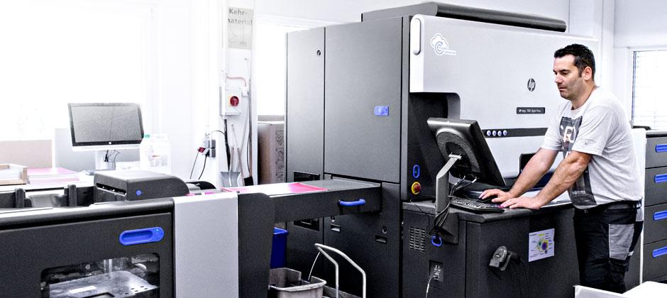 Mitarbeiter arbeitet an Digitaldruckmaschine
